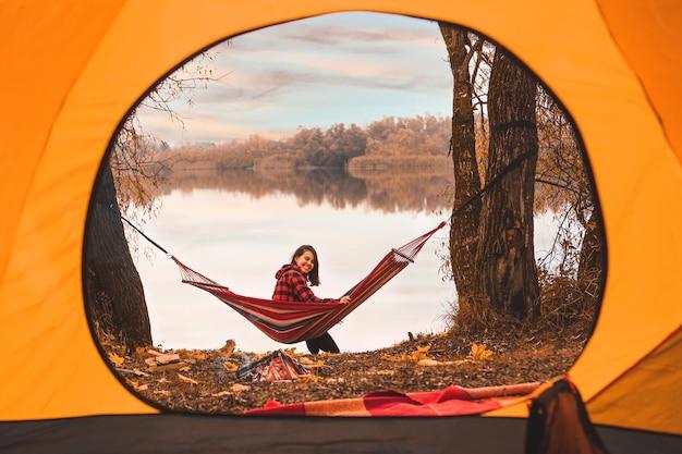Vue depuis la tente femme assise sur le hamac avec lac sur fond automne automne saison