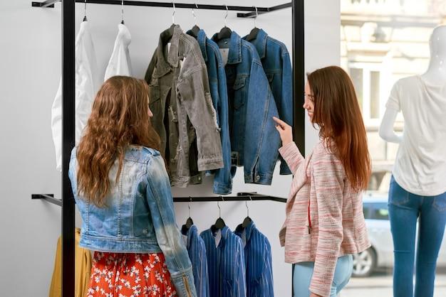 Vue de derrière de deux filles achetant des vêtements dans la boutique.