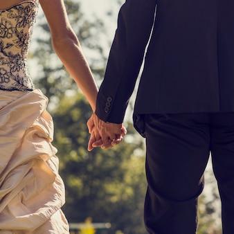 Vue de derrière du couple de jeunes mariés, de la mariée et du marié, se tenant la main à l'extérieur par une journée ensoleillée, effet rétro délavé.