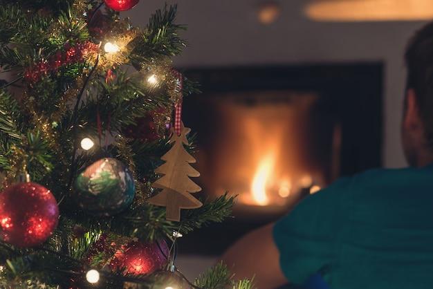 Vue de derrière du jeune homme assis devant la cheminée avec feu et arbre de noël à côté de lui.