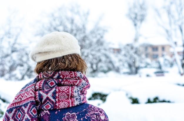 Vue de derrière d'une femme marchant dans la ville lors d'une chute de neige.