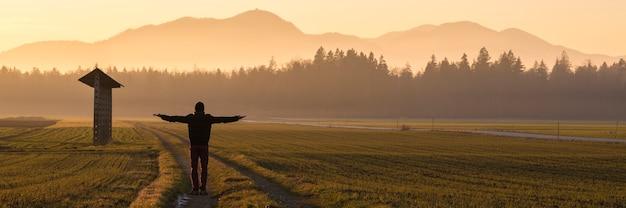 Vue de derrière d'un homme en veste d'hiver et chapeau debout sur une route de campagne au milieu d'un paysage magnifique avec une botte de foin sur sa gauche avec les bras tendus au crépuscule.