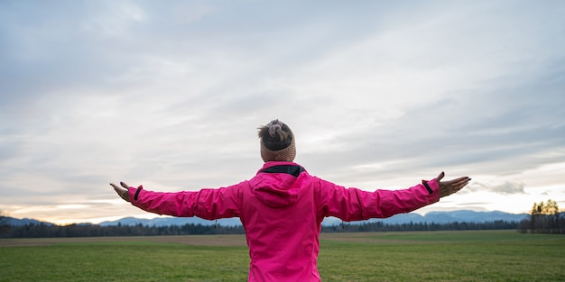 Vue de derrière d'une jeune femme en veste rose debout, les bras grands ouverts sous un ciel du soir.