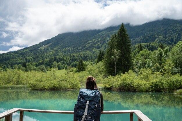 Vue de derrière d'une randonneuse avec sac à dos debout au bord d'un magnifique lac vert profitant de la vue et se reposant.