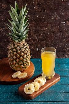Vue de dessous ananas frais tranches d'ananas sec jus sur planches de bois