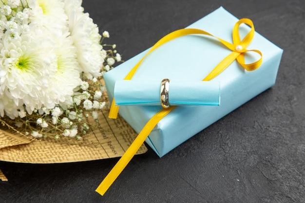 Vue de dessous bague de fiançailles défilement papier de souhaits sur bouquet de fleurs cadeau sur fond noir