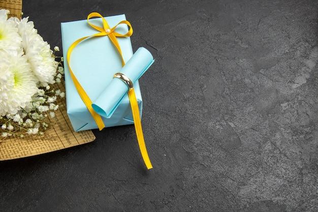 Vue de dessous bague de fiançailles défilement papier de souhaits sur bouquet de fleurs cadeau sur fond sombre espace libre