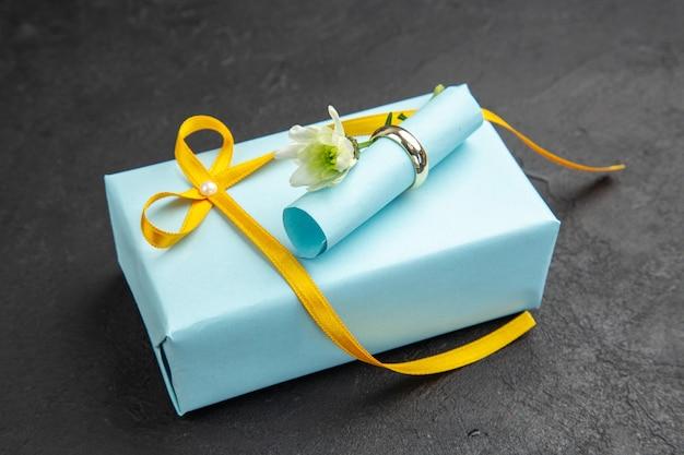 Vue de dessous bague de fiançailles défilement papier de souhaits sur cadeau sur fond sombre