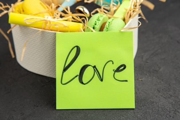 Vue de dessous boîte en forme de coeur avec des macarons en anneau enroulé des notes autocollantes amour écrit sur une note collante sur fond sombre