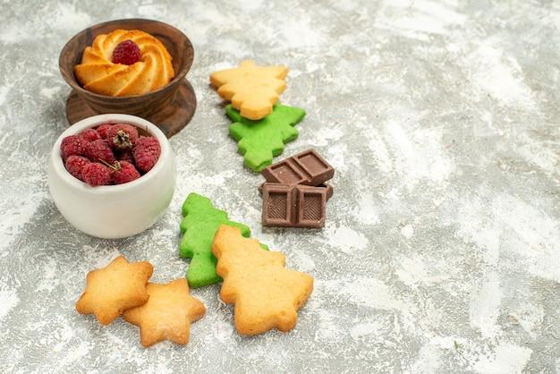 Vue de dessous bol de biscuits d'arbre de noël avec des framboises sur un espace de copie de surface grise