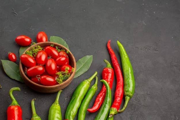 Vue de dessous un bol de tomates cerises poivrons rouges et verts chauds et feuilles de laurier sur fond noir