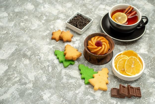 Vue de dessous des bols de biscuits au thé au citron et à la cannelle avec des tranches de chocolat et de citron sur une surface grise