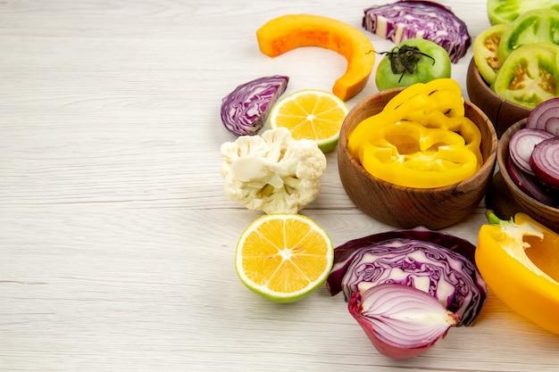 Vue de dessous bols en bois avec légumes coupés chou-fleur oignon chou rouge tomate verte poivron jaune citron sur table blanche avec espace libre