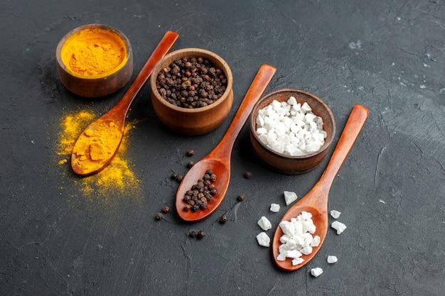 Vue de dessous bols avec cuillères en bois de sel sae au curcuma poivre noir sur une surface sombre
