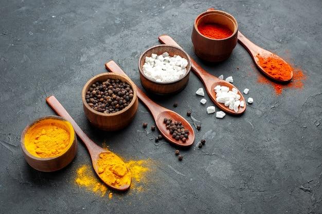 Vue de dessous bols avec curcuma poivre noir sae sel poivre rouge poudre cuillères en bois sur surface sombre
