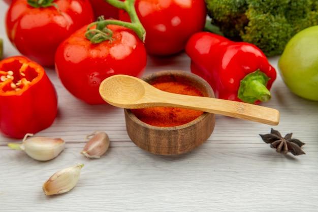Vue de dessous branche de tomate brocoli anis ail cuillères en bois sur bol d'épices sur table grise