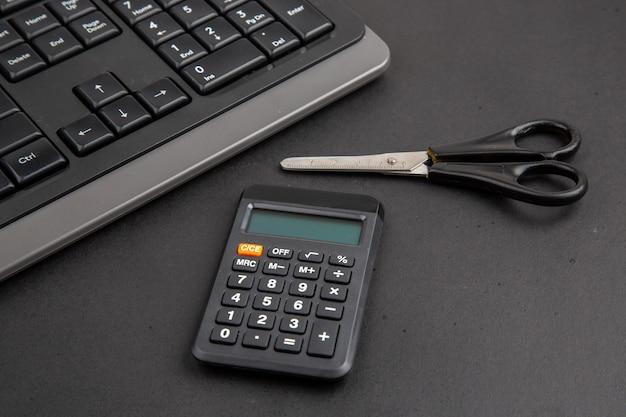 Vue de dessous le bureau noir fourre des ciseaux de calculatrice de clavier sur une table sombre