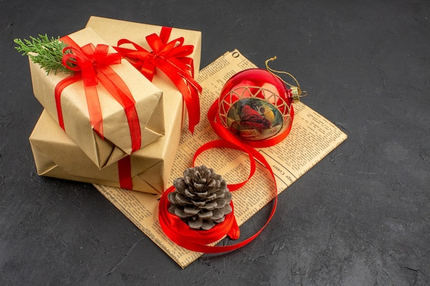 Vue de dessous cadeaux de noël en ruban de papier brun jouet d'arbre de noël sur papier journal sur dark