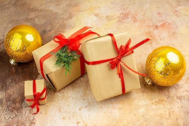Vue de dessous cadeaux de noël en ruban de papier brun jouet d'arbre de noël sur papier journal sur fond sombre