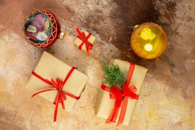 Vue De Dessous Cadeaux De Noël En Ruban De Papier Brun Jouet D'arbre De Noël Sur Papier Journal Sur Fond Sombre Photo gratuit