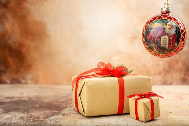 Vue de dessous cadeaux de noël en ruban de papier brun jouets d'arbre de noël sur papier journal sur beige