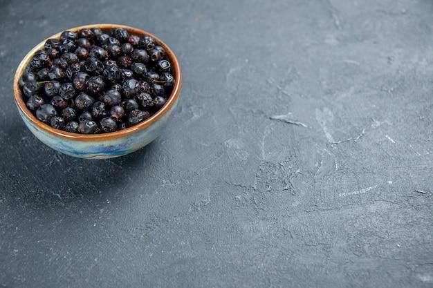 Vue de dessous de cassis dans un bol sur une surface sombre avec place libre