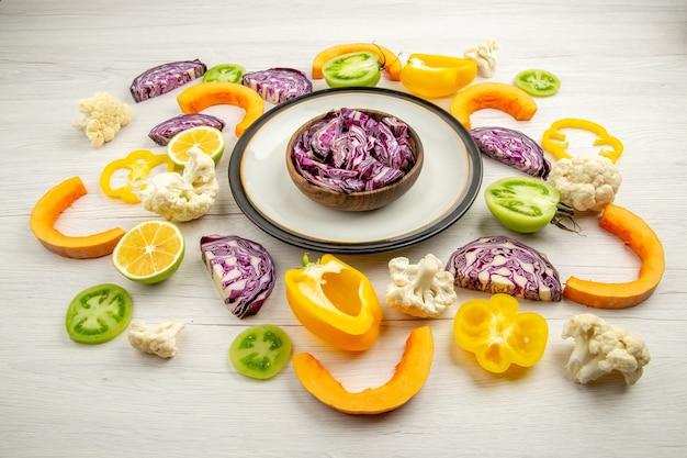 Vue de dessous des choux rouges coupés dans un bol sur un plateau rond de légumes coupés sur une surface blanche