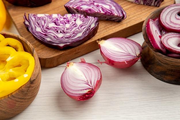 Vue de dessous des choux rouges hachés coupés en oignon des poivrons coupés dans des bols sur une surface blanche