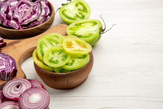 Vue de dessous des choux rouges hachés coupés de l'oignon des tomates vertes coupées dans des bols sur une surface blanche