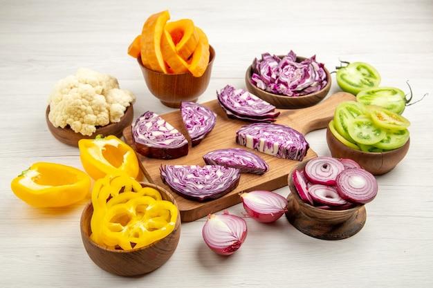 Vue de dessous des choux rouges hachés sur une planche à découper des poivrons coupés de la citrouille coupée de l'oignon coupé dans des bols sur une surface blanche