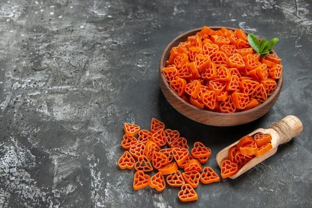 Vue de dessous coeurs rouges de pâtes italiennes dans un bol cuillère en bois sur une surface sombre