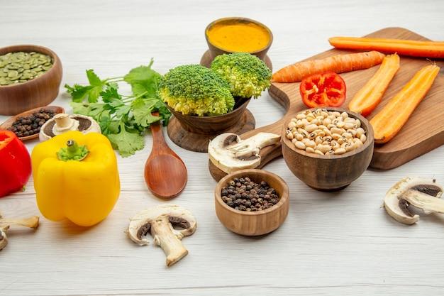 Vue de dessous couper des carottes jaunes sur une planche à découper des champignons poivre noir dans des bols de cuillère en bois avec des épices et des haricots brocoli sur une table grise
