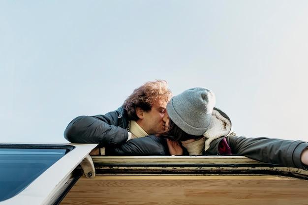 Vue de dessous couple s'embrassant sur une camionnette à l'extérieur