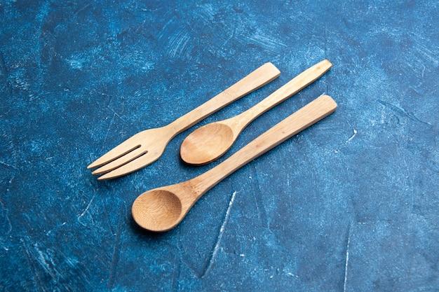 Vue de dessous couteau cuillère fourchette en bois sur surface bleue avec espace libre