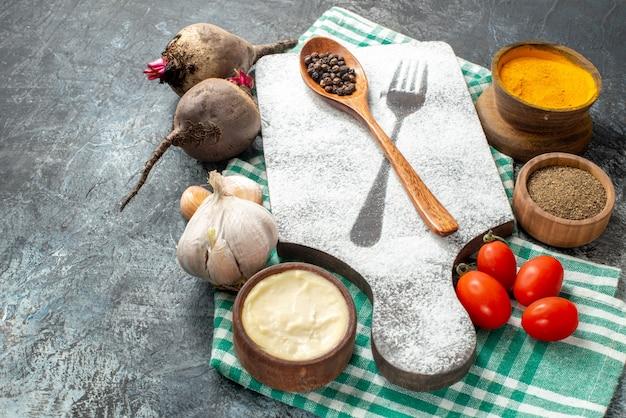 Vue de dessous cuillère en bois sur planche à découper épices dans des bols betteraves à l'ail tomates cerises sur mur gris