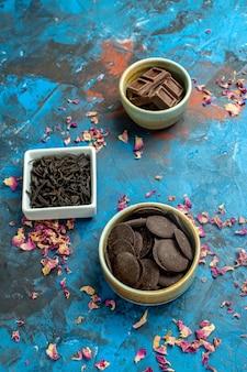 Vue de dessous différents chocolats dans de petits bols sur une surface rouge bleu