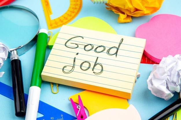 Vue de dessous du bureau coloré bourre bon travail écrit sur papier sur fond bleu