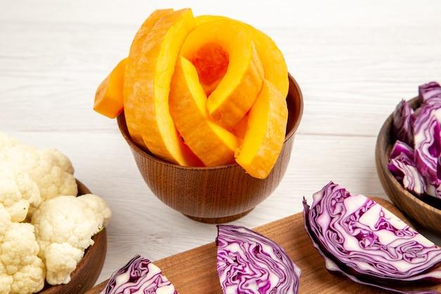 Vue de dessous du chou-fleur à la citrouille hachée du chou rouge coupé à bord dans des bols sur une surface blanche