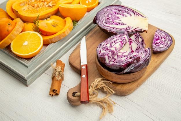 Vue de dessous du chou rouge haché dans un bol couteau sur une planche à découper des fruits coupés à la cannelle sur un cadre sur une table grise