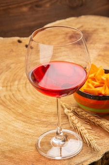 Vue de dessous du vin dans des copeaux de verre à vin ballon dans un bol sur une surface en bois
