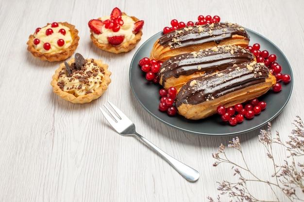 Vue de dessous éclairs au chocolat et groseilles sur la plaque grise cookies une fourchette sur la table en bois blanc