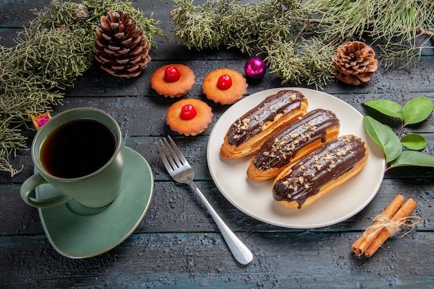 Vue de dessous éclairs au chocolat sur plaque ovale blanche branches de sapin et cônes jouets de noël une fourchette à la cannelle une tasse de thé et petits gâteaux sur table en bois foncé