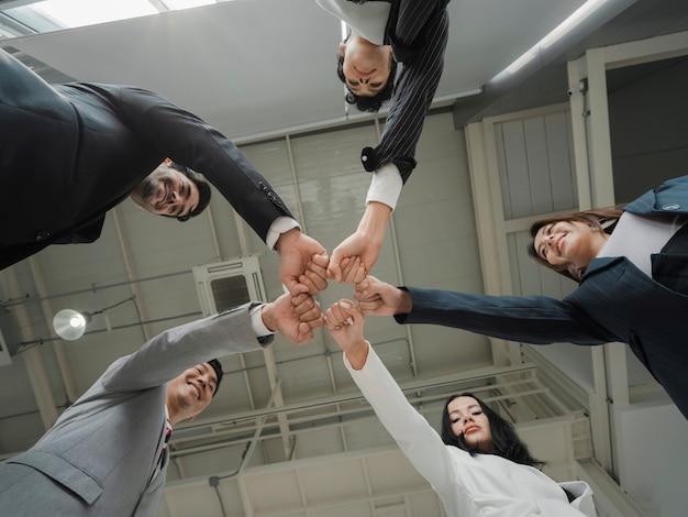 Vue de dessous d'une équipe d'hommes d'affaires diversifiés et heureux tenant les poings en cercle, exprimant l'unité et le pouvoir dans le travail d'équipe, des hommes d'affaires multiethniques engagés dans une activité de consolidation d'équipe lors du briefing