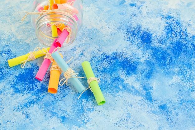 Vue de dessous faites défiler les papiers de souhaits colorés dispersés dans un pot sur fond bleu avec espace libre