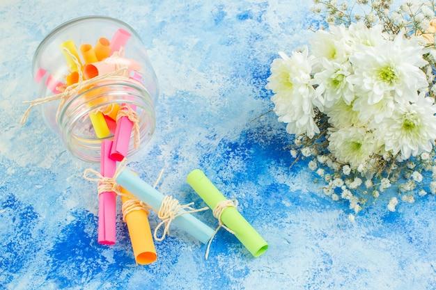 Vue de dessous faites défiler les papiers de souhaits colorés dispersés à partir de fleurs en pot sur fond bleu
