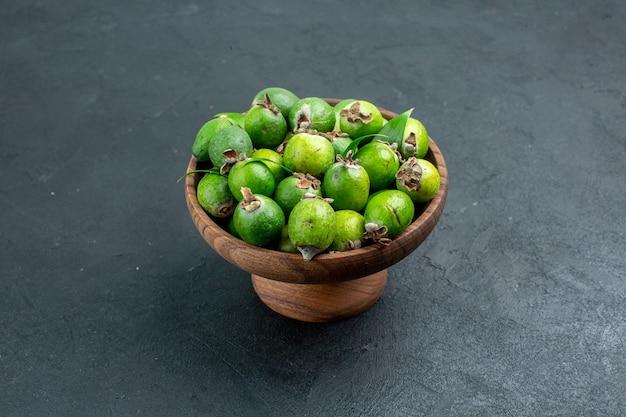 Vue de dessous feijoas frais dans un bol en bois sur une surface sombre avec espace de copie
