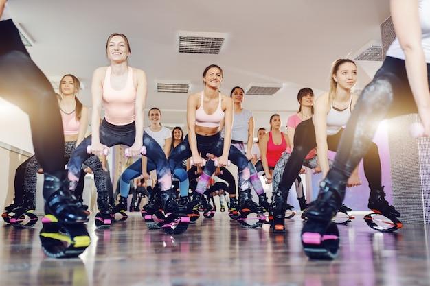 Vue de dessous des femmes faisant des exercices avec des haltères tout en portant des chaussures de sauts kangoo. intérieur du studio de remise en forme.