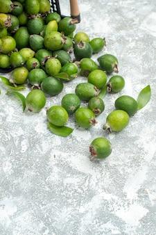 Vue de dessous des feykhoas frais éparpillés du panier sur une surface grise avec espace de copie