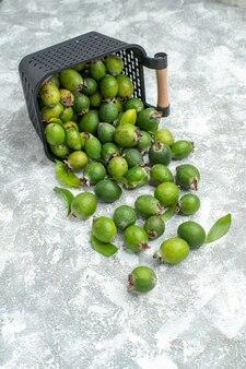 Vue de dessous des feykhoas frais éparpillés du panier sur une surface grise
