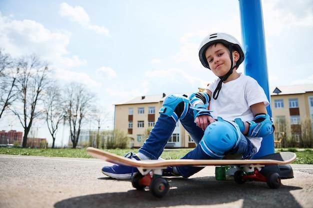Vue de dessous d'un garçon souriant en tenue de protection de skateur assis sur une planche à roulettes et regardant à l'avant